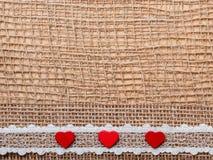 在抽象布料背景的红色心脏 库存照片