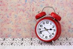 在抽象桃红色背景的红色减速火箭的闹钟 库存照片