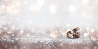在抽象银色闪烁的bokeh背景的婚戒 免版税库存照片