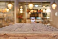 在抽象餐馆前面的木桌点燃背景 图库摄影
