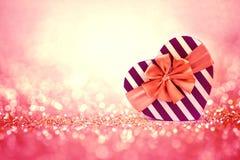 在抽象轻的闪烁backgrou的红色心脏形状礼物盒 库存图片