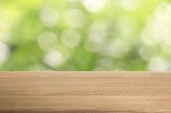 在抽象绿色背景的老木桌 免版税库存照片