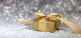 在抽象bokeh光和闪烁背景的圣诞节金黄礼物盒 图库摄影
