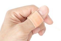 在拇指分裂背景的绷带 免版税库存图片