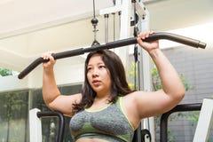 在拉特的肥胖妇女减重锻炼训练拉下在健身健身房的机器 免版税库存照片