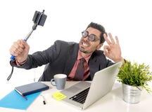 在拍与手机照相机和棍子的办公桌的滑稽的书呆子商人selfie照片 免版税库存照片
