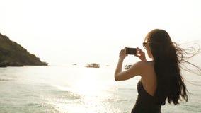 在拍摄日落的照片与智能手机的海滩海岛上的妇女游人在度假小船和地平线视图 库存照片