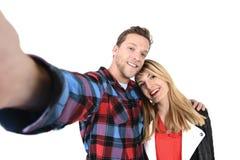 在拍浪漫自画象selfie照片的爱的年轻美好的美国夫妇与手机一起 库存图片