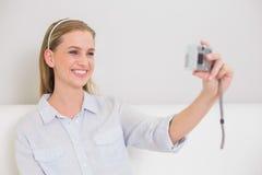 在拍照片的她自己的长沙发的愉快的偶然白肤金发的开会 免版税库存照片