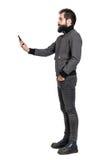 在拍selfie照片的灰色夹克的严肃的时髦的punker 侧视图 免版税库存照片