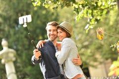 在拍selfie照片的爱的夫妇在公园 免版税库存照片