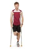在拐杖的体育人受伤的健身 免版税图库摄影