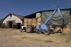 在拖拉机旁边的农场 图库摄影