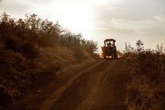 在拖拉机的农夫乘驾 库存图片