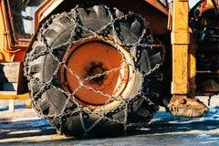 在拖拉机轮胎的雪链子 免版税库存照片