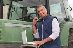 在拖拉机附近的农夫 免版税库存图片