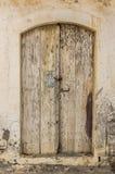 在拖着脚走路的墙壁的老木材门 免版税库存照片
