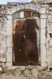 在拖着脚走路的墙壁的老白色生锈的门 免版税图库摄影