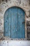 在拖着脚走路的墙壁的老蓝色木材门 图库摄影