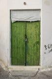 在拖着脚走路的墙壁的老绿色木材门 免版税库存照片