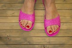 在拖鞋的女性脚在木地板或背景上 免版税库存图片