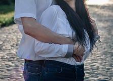 在拥抱和亲吻在牛仔裤和白色衬衫的爱的愉快的夫妇 免版税库存照片