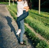 在拥抱和亲吻在牛仔裤和白色衬衫的爱的愉快的夫妇 免版税图库摄影