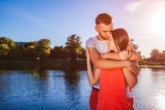 在拥抱和微笑由河的爱的愉快的夫妇对日落 免版税库存照片