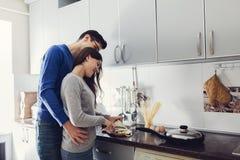 在拥抱和烹调晚餐的厨房的年轻夫妇 库存照片