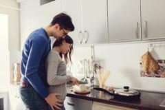 在拥抱和烹调晚餐的厨房的年轻夫妇 免版税图库摄影