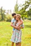 在拥抱在一个夏天的爱美丽的年轻人的一对夫妇在一个晴天停放 免版税库存图片