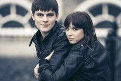 在拥抱在城市街道的爱的愉快的年轻夫妇 库存照片