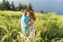 在拥抱在大绿草的爱的夫妇 在热情地拥抱的爱的夫妇 两个恋人的期待已久的会议草的 免版税库存照片