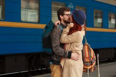 在拥抱在火车站的街道的一对愉快的夫妇的旅行的以后遭遇 美好的晚上温暖的阳光 库存照片