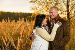 在拥抱在秋天日落的爱的夫妇 免版税库存图片