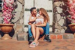 在拥抱坐的爱的混合的族种夫妇由咖啡馆门户外 阿拉伯走在城市的男人和白人妇女 库存图片