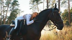 在拥抱她和抚摸的马的美好的女孩骑马 股票视频