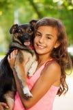 在拥抱小犬座的十几岁的女孩画象 免版税库存图片
