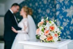 在拥抱新娘和新郎背景的婚礼花束  免版税库存照片