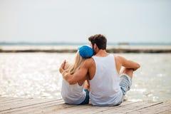 在拥抱的海滩的爱恋的夫妇,当看海时 免版税库存图片