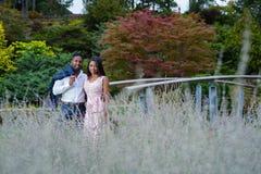在拥抱的爱的年轻夫妇在淡紫色庭院里 免版税库存图片