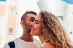 在拥抱的爱的混合的族种夫妇户外 亲吻面颊的愉快的阿拉伯人白人妇女 浪漫关系 免版税库存图片