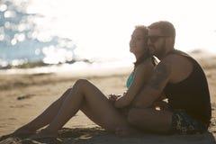 在拥抱观看的日出日落的浪漫夫妇一起 爱人妇女年轻人 库存照片