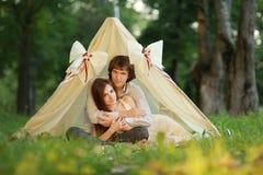 在拥抱里面精密帐篷的爱夫妇的夏天晚上在公园 免版税库存图片