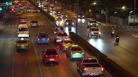 在拥挤的街上的运输流量在商业区在晚上 在交叉点的汽车通行 汽车点燃照亮 影视素材