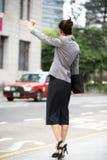 在拥挤的街的女实业家称赞的出租汽车 库存图片