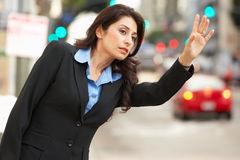 在拥挤的街的女实业家称赞的出租汽车 免版税库存图片