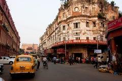 在拥挤的街的老旅馆前面被停止的出租车 免版税库存图片