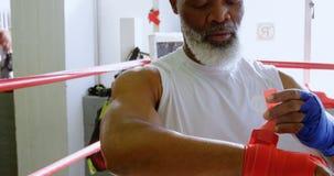 在拳击台4k的老人佩带的腕子套 影视素材