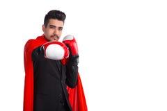 在拳击手套和超级英雄红色斗篷的商人举手对照相机 免版税库存照片
